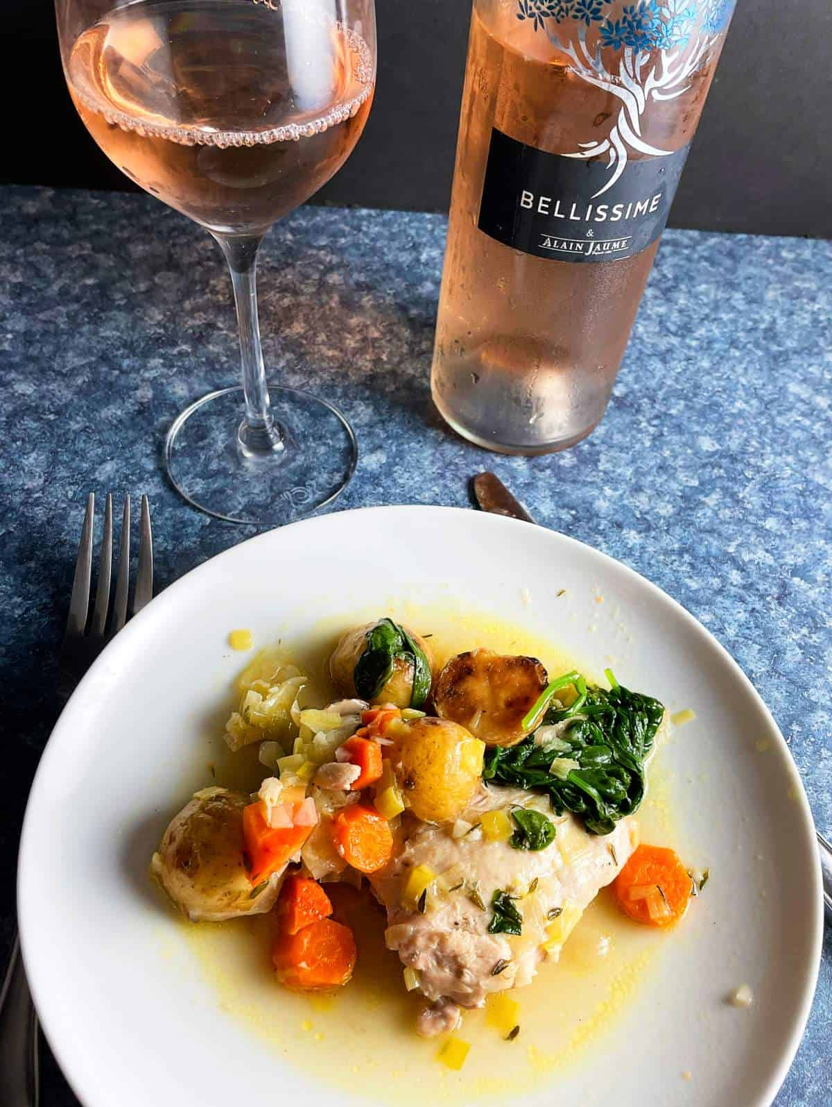 braised chicken thighs served with carrots, spinach and potatoes. A rosé wine is in the background.