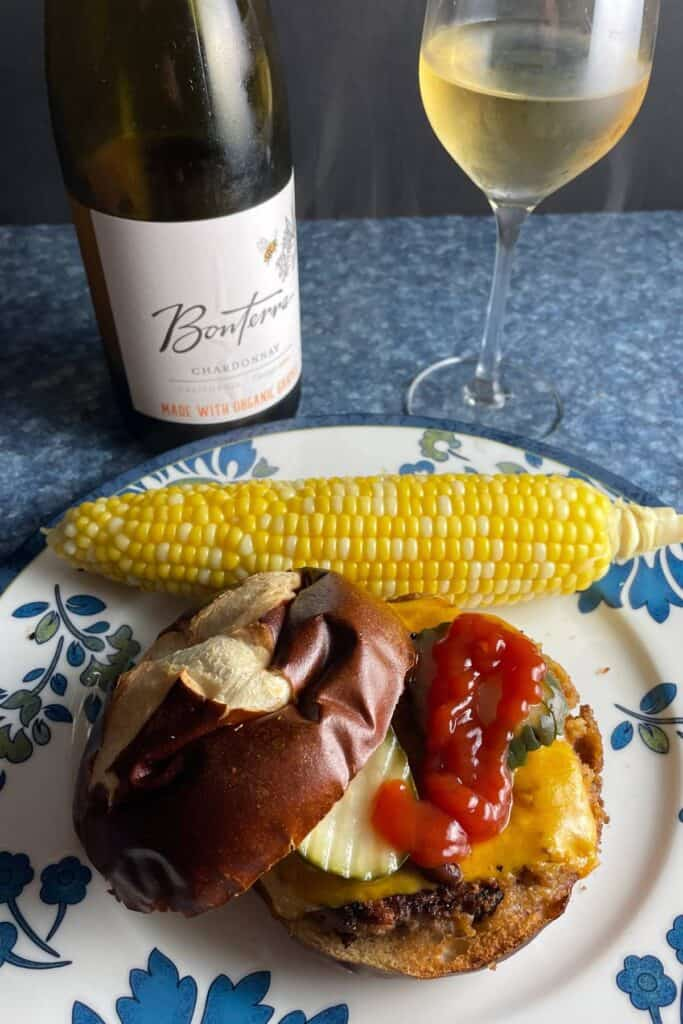 Veggie burger in a bun photographed from above, served with a Bonterra Chardonnay white wine.