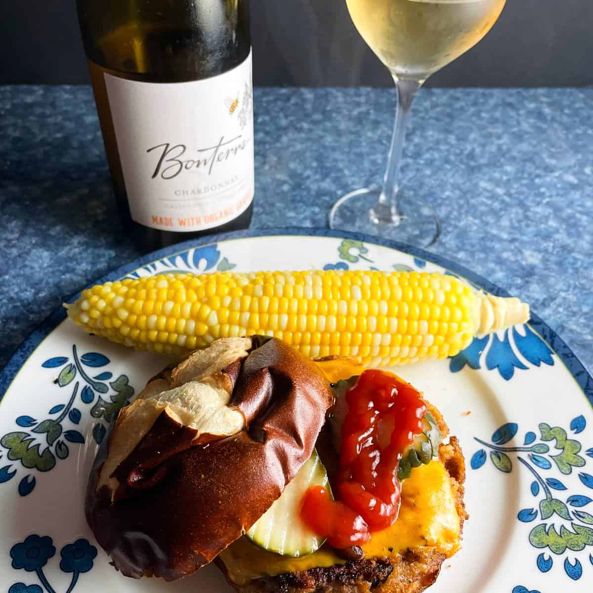 veggie burger with a side of corn on the cob, served with Bonterra Chardonnay white wine.