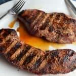 grilled sirloin steaks on a white platter