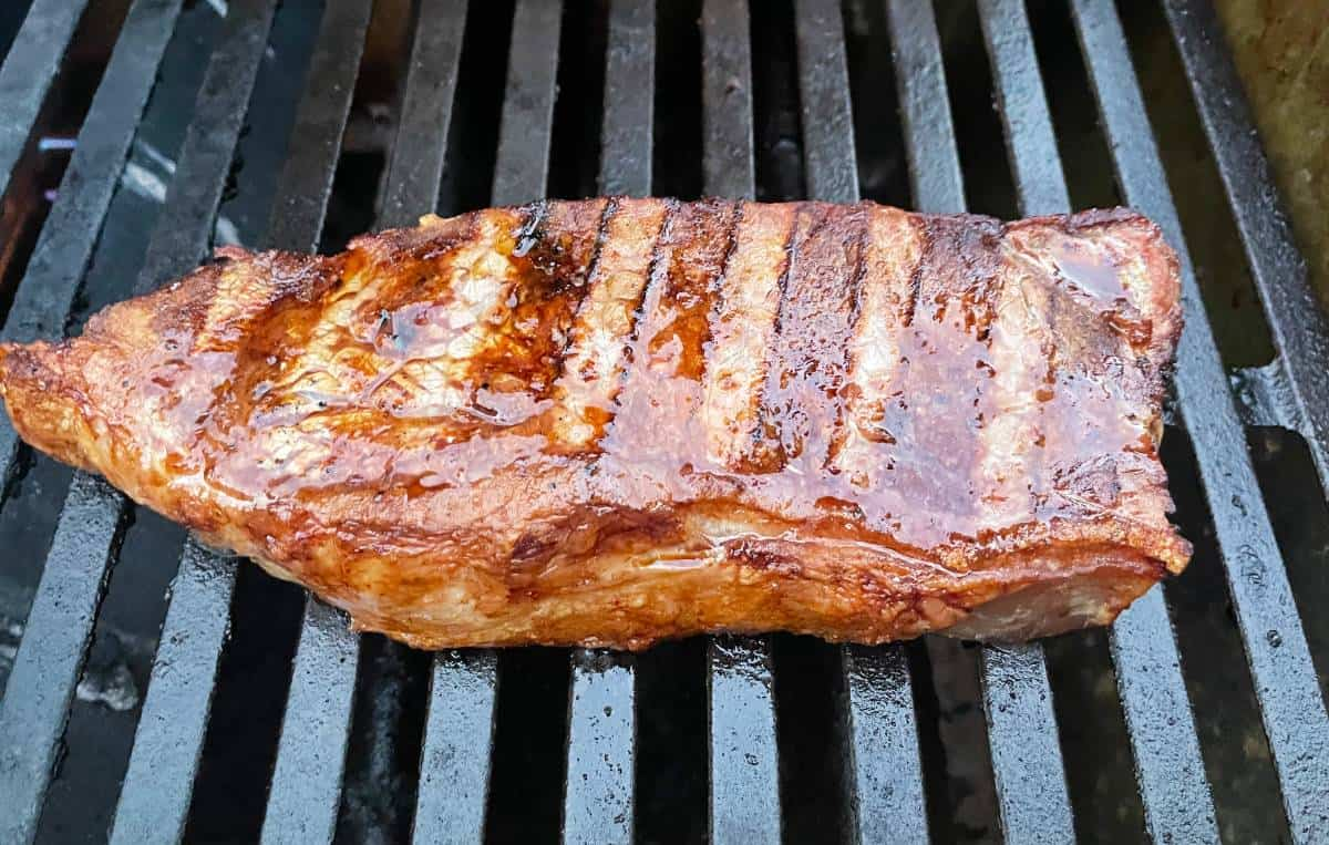 NY strip steak cooking on a grill with black grates.