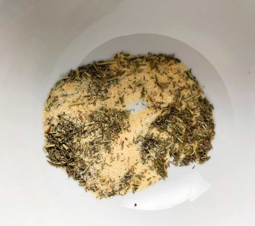 garlic powder, salt, dried thyme and rosemary combined in a white bowl to make a spice rub.