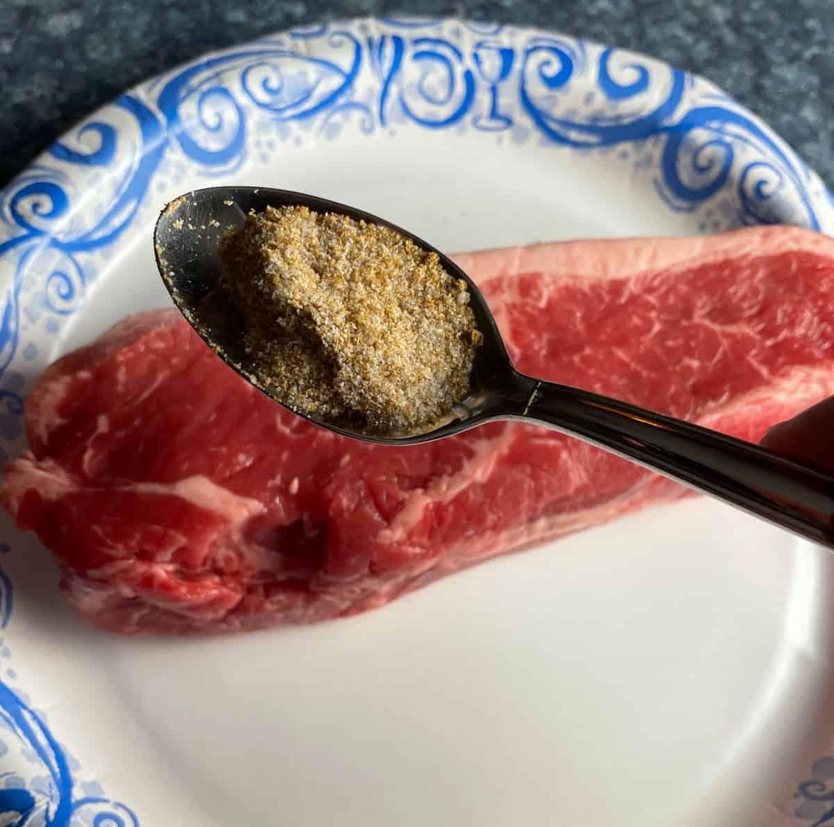teaspoon of dry steak rub over a piece of raw steak.