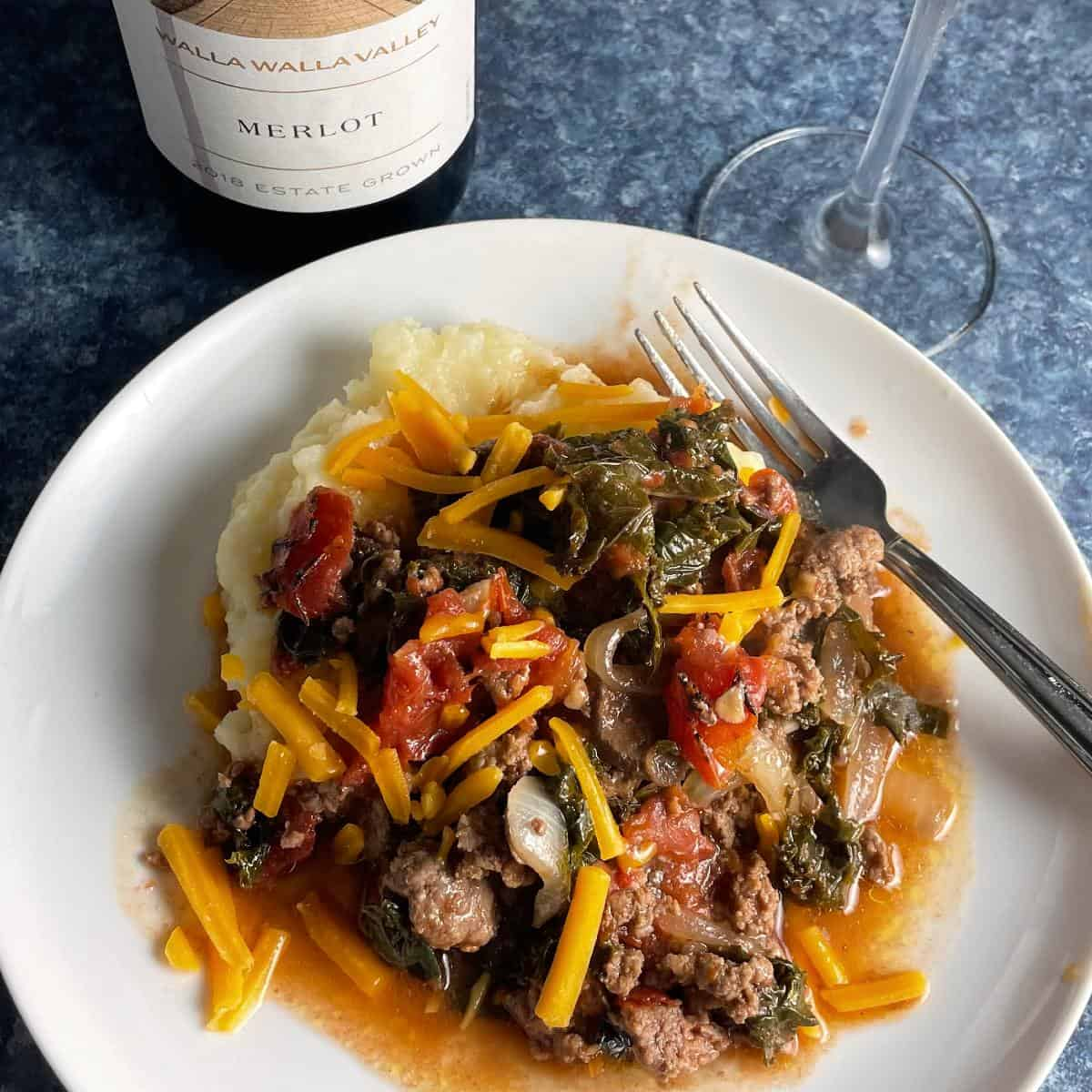 ground beef and kale topped with cheddar cheese, served over mashed potatoes. Red Merlot wine in the background.