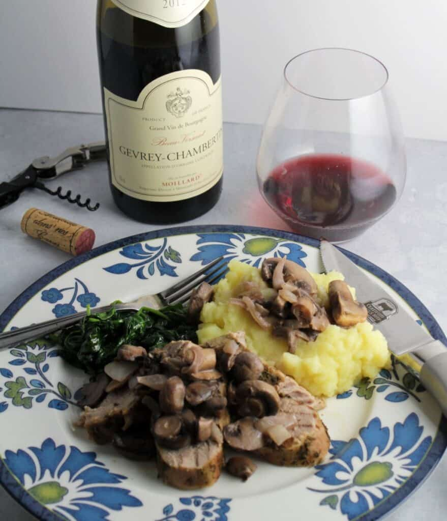 pork tenderloin topped with mushrooms, served with mashed potatoes and greens. Bottle and glass of red Burgundy wine in background.