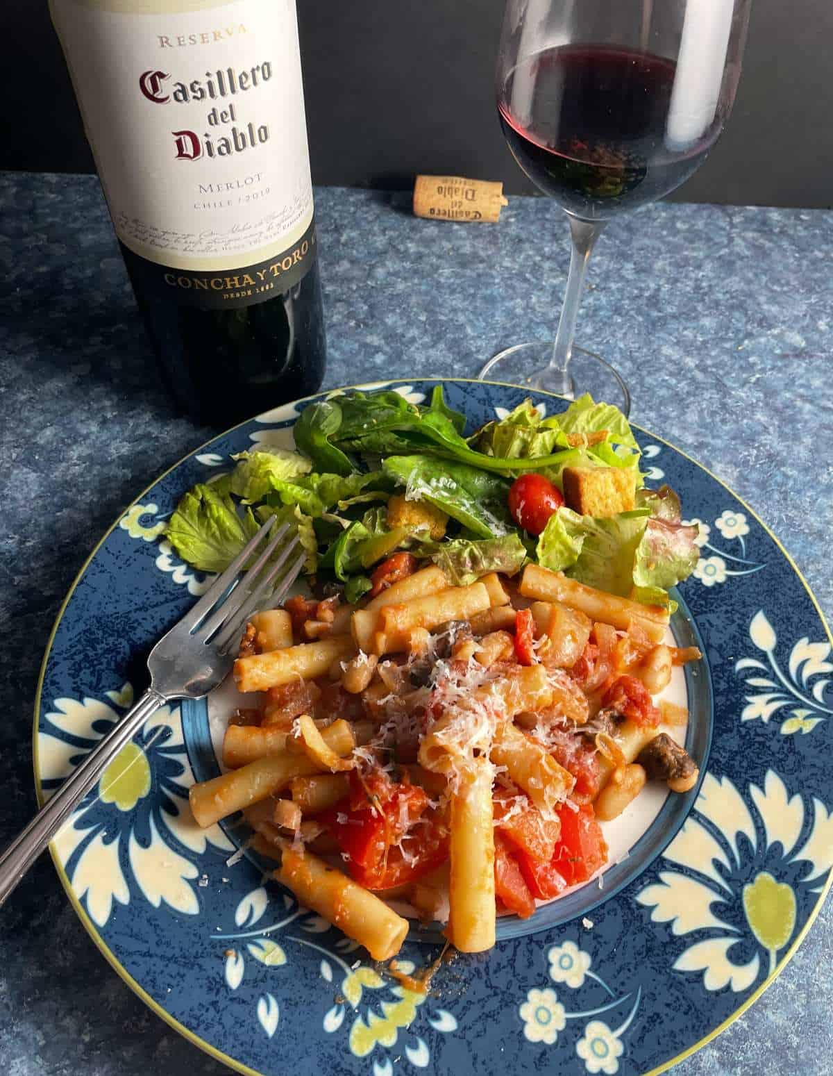 ziti pasta with tomato sauce and white beans, served with a side salad and a Merlot red wine.