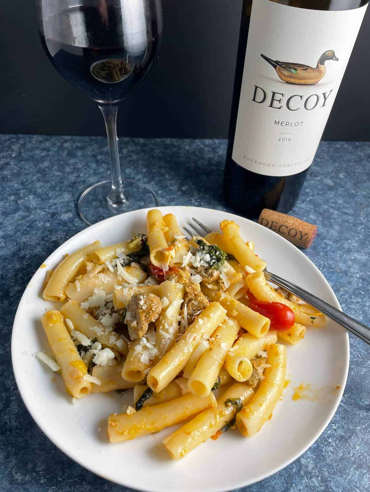 ziti pasta with sausage and greens on a white plate, served with a Merlot red wine.
