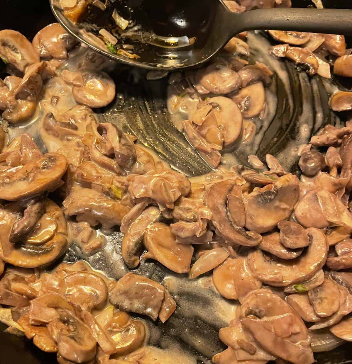mushrooms with cream sauce in a black skillet.