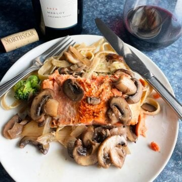 salmon topped with mushrooms, served with pasta and a red Merlot wine.