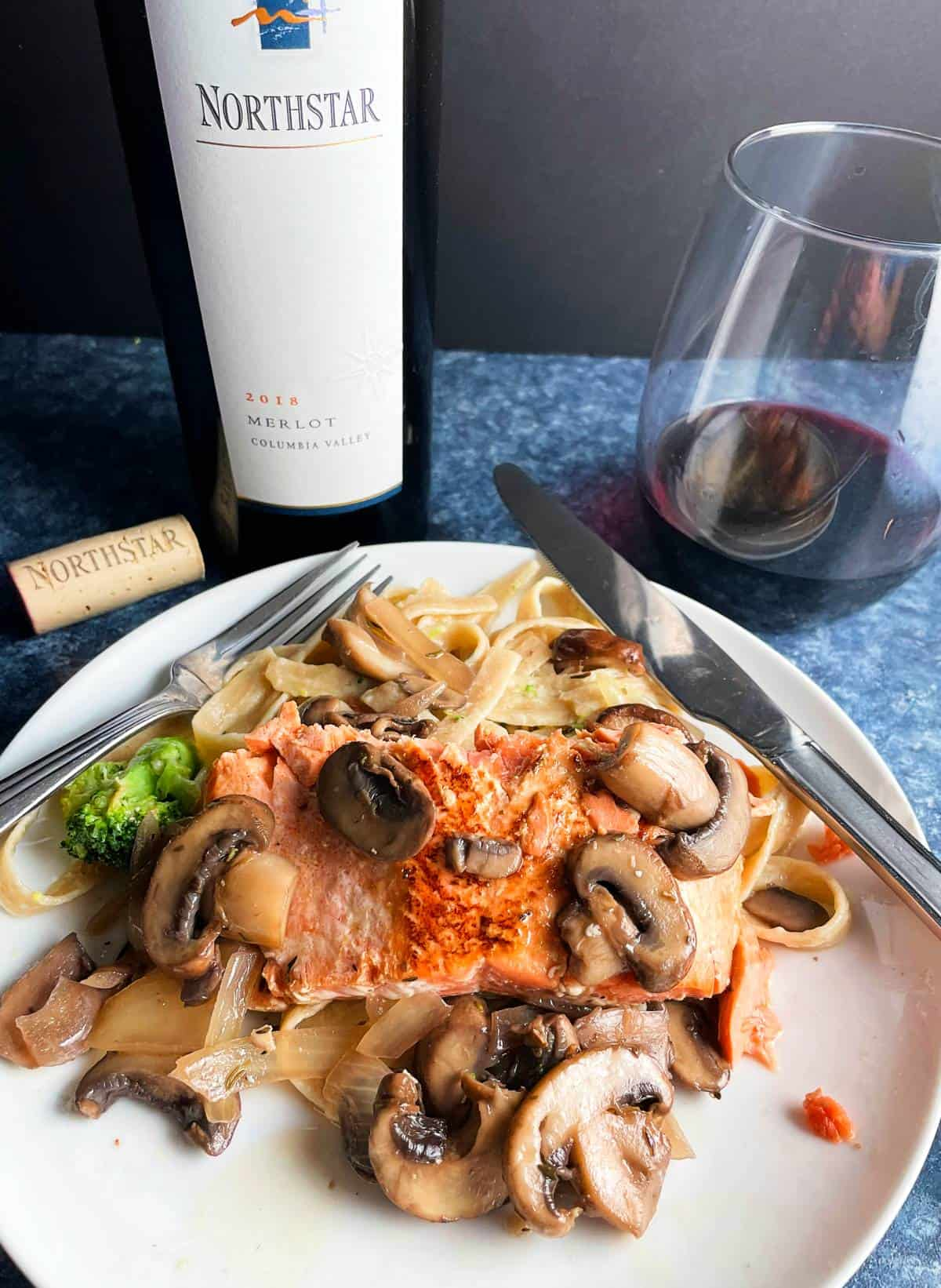 seared salmon topped with mushrooms, served with fettuccine. Glass and bottle of Merlot red wine in the background.
